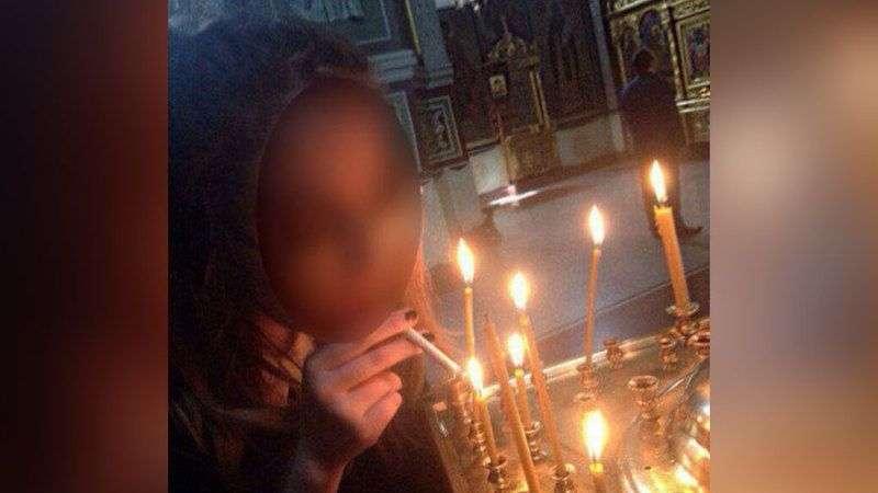 Девушка прикурила сигарету от горящей свечи в храме