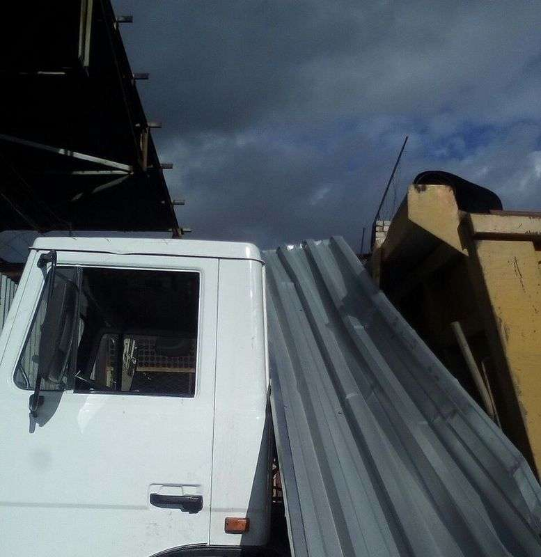 часть забора из профлиста ветром закинуло на грузовой автомобиль