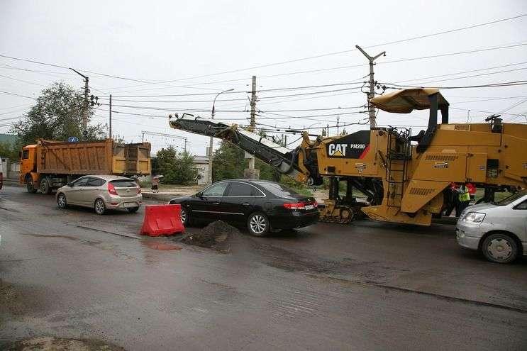 На улице Качинцев половина проезда уже покрыта первым слоем асфальтобетона